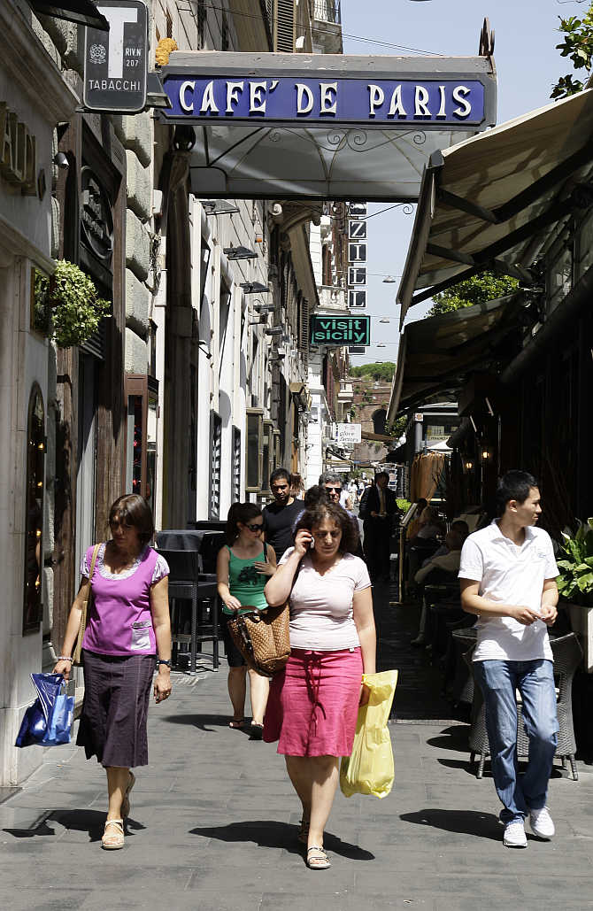 Shoppers walk past the Cafe De Paris on Via Veneto in Rome, Italy.