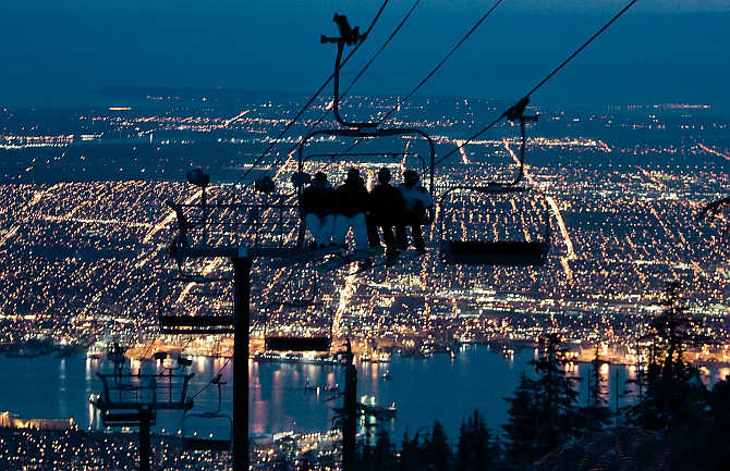 Snowboarders ride a chair lift on one of the many snow runs during night skiing on Grouse Mountain with the city of Vancouver, British Columbia down below, Canada.