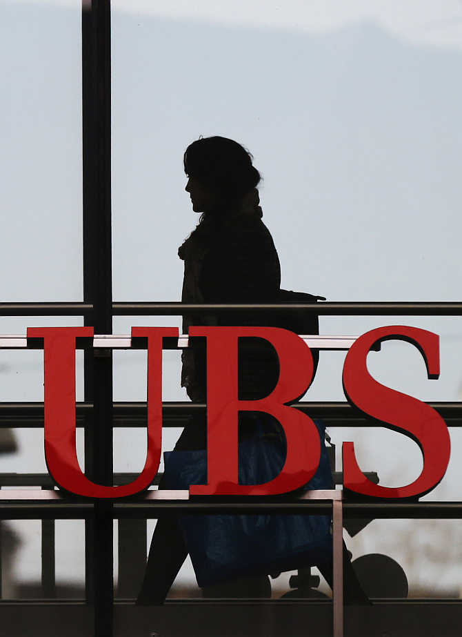 An employee walks past a logo of Swiss bank UBS in Zurich, Switzerland.