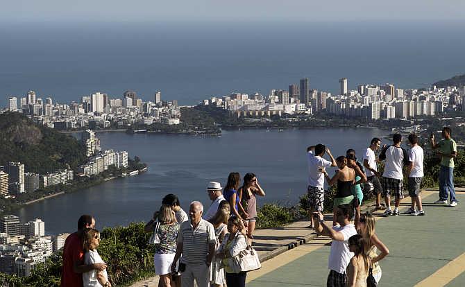Tourists take pictures with the Rodrigo de Freitas Lagoon in the background in Rio de Janeiro, Brazil.