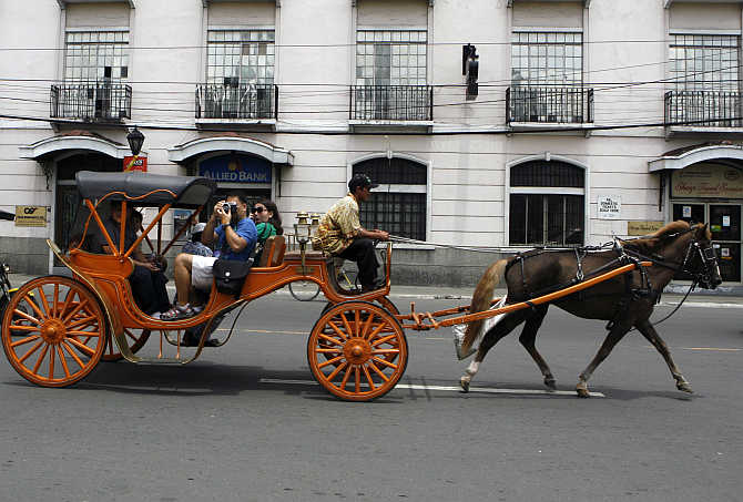 Tourists ride on a 'Kalesa' a horse drawn carriage in Manila's historic Intramuros also known as 'Walled city', the Philippines.