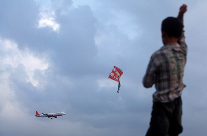 A boy flies a kite from a rooftop overlooking Chhatrapati Shivaji International Airport, as a Boeing 737 aircraft belonging to Air India comes in to land in Mumbai.