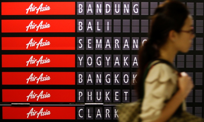 A commuter passes an AirAsia advertisement showing the destinations that the budget carrier flies to, at a train station in Singapore.