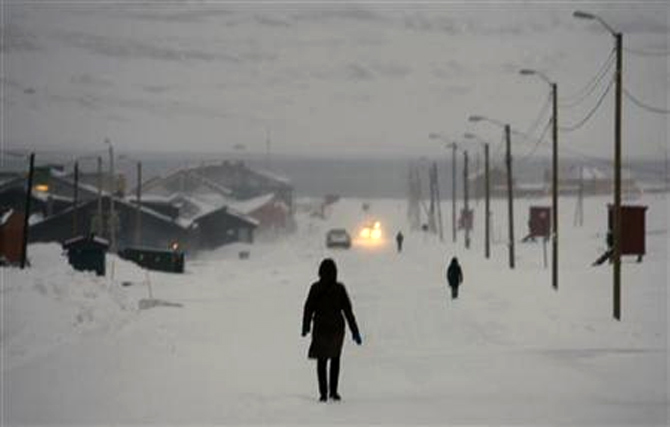Pedestrians walk down the main street in the arctic town of Longyearbyen.