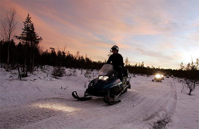 Tourists drive snowmobiles during an arctic safari at Arctic Circle near Rovaniemi, northern Finland.