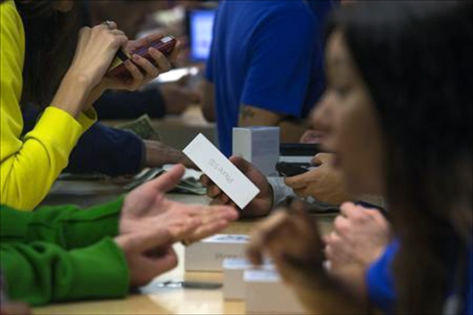 Customers purchase the iPhone 5s at the Apple retail store on Fifth Avenue in Manhattan, New York.