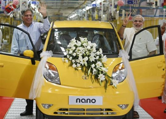 Ratan Tata (L), chairman of the Tata Group, and Gujarat's chief minister Narendra Modi wave as they stand beside the Tata Nano car during the inauguration ceremony of a new plant for the Tata Nano at Sanand in Gujarat