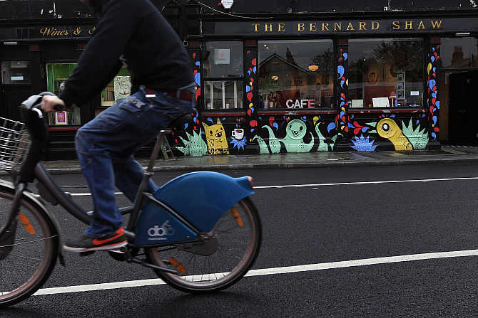 A cyclist rides past the Coffee To Get Her restaurant near Dublin city centre which becomes a bar and club in the evenings, Ireland.
