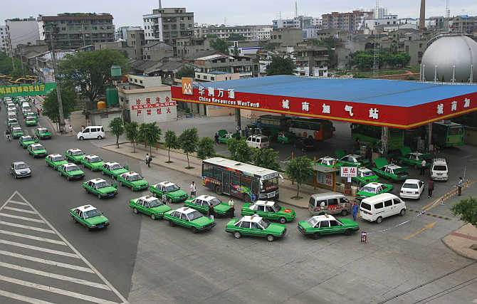 Taxis wait to fill their tanks at a petrol pump in Suining, Sichuan province, China.