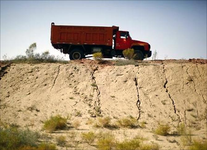 A truck drives along a road near the dried up Shiyang river on the outskirts of Minqin town, Gansu province.