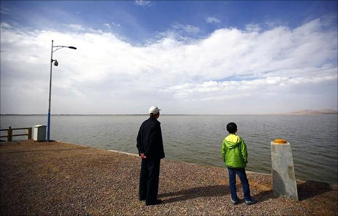 Visitors look at the Hongyashan water reservoir on the outskirts of Minqin town, Gansu province.