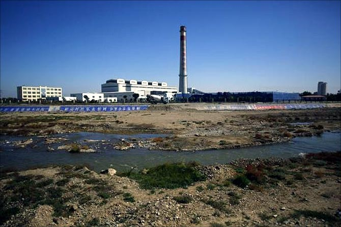 A section of the Shiyang river is seen next to a coal thermoelectric plant in Wuwei, Gansu province.