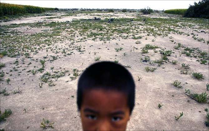 A child stands in a field near the dried up Shiyang river on the outskirts of Minqin town, Gansu province.