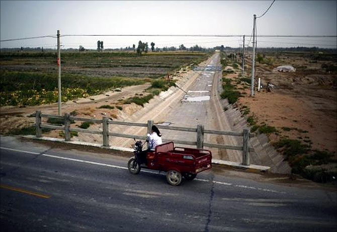 A farmer drives an electric tricycle across an irrigation canal near the dried up Shiyang river on the outskirts of Minqin town, Gansu province.