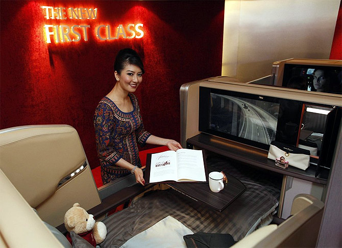 A Singapore Airlines stewardess poses at a first class cabin seat during the launch of their new generation of cabin products at ChangiAirport in Singapore.