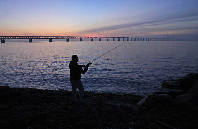 A man fishes near Oresund bridge, which links the city of Malmo in Sweden to Copenhagen, the capital of Denmark, and has a total length of 7,845 metres.