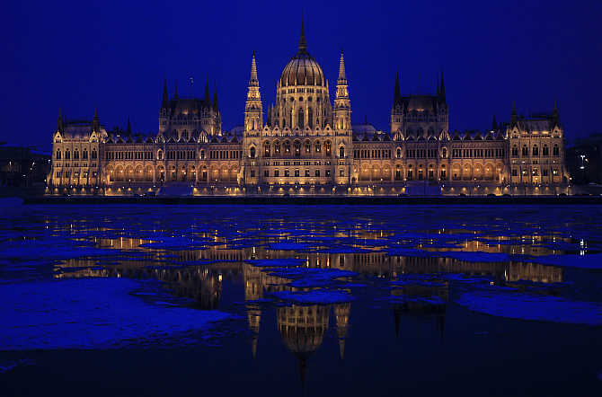 Parliament building is reflected on the icy Danube river in Budapest, Hungary.