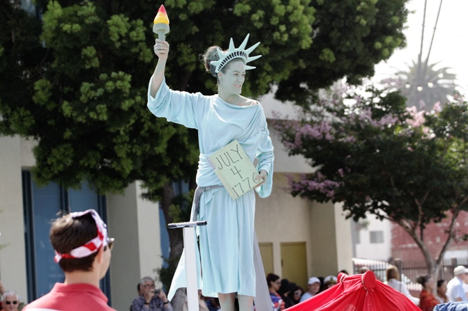 A woman dressed as the Statue of Liberty rides on a float during Santa Monica's seventh annual Fourth of July parade in Santa Monica, California.