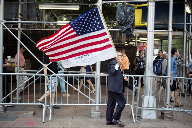 A man walks with a U.S. flag before a moment of silence honoring the victims of the September11 attacks outside the World Trade Center site in New York.