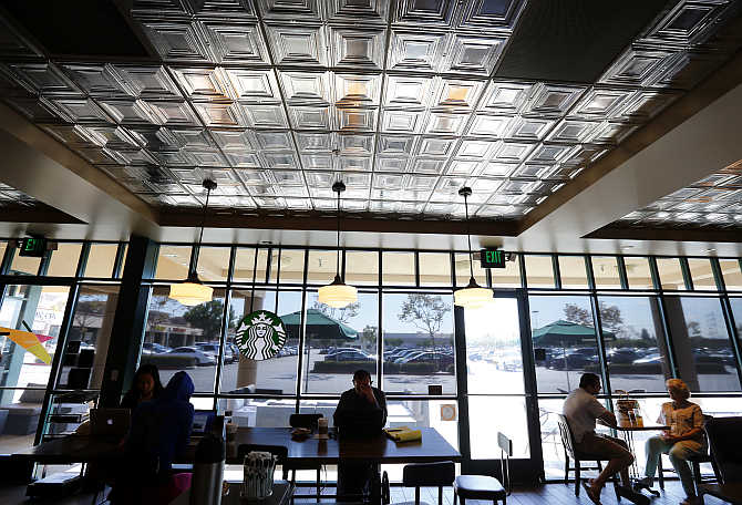 Customers enjoy their drinks inside a Starbucks coffee shop in Fountain Valley, California.