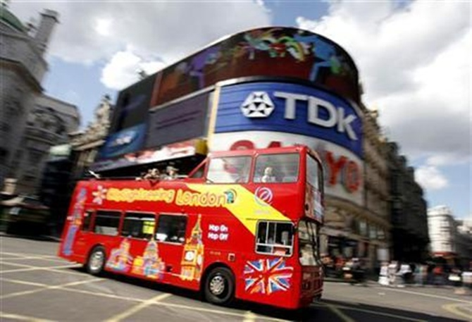A sightseeing bus passes through London's Piccadilly Circus.