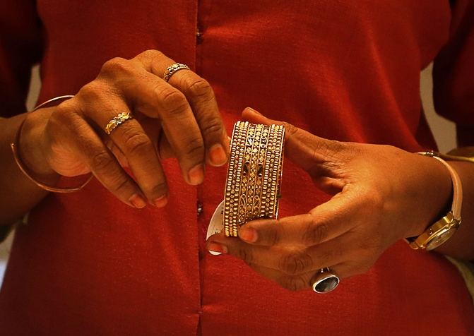 An employee shows a gold bangle to a customer inside a jewellery showroom in Mumbai.