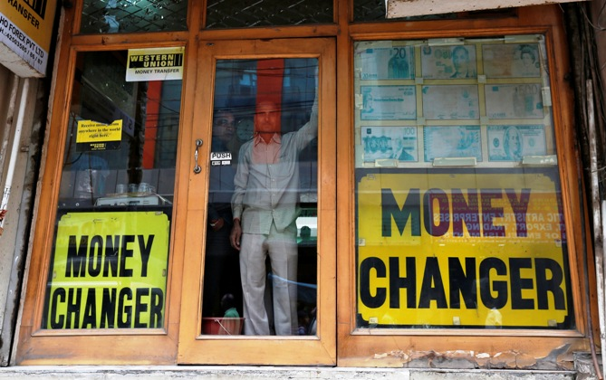 Two men look out from the glass door of a currency exchange shop in New Delhi.