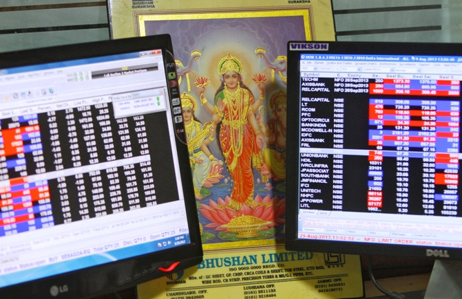 An image of Lakshmi, the Hindu goddess of wealth and prosperity, is placed between monitors displaying share price index at a share trading market in Chandigarh.