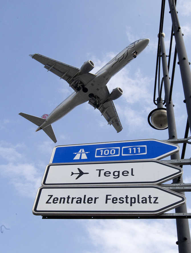 A plane flies above a traffic sign as it approaches Berlin's Tegel airport for landing in Germany.