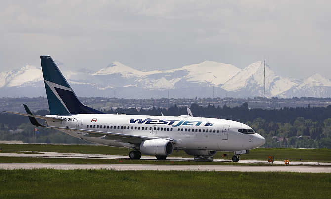 A Westjet airline plane lands at the Calgary International Airport in Calgary, Alberta, Canada.