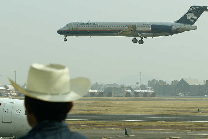 A plane spotter watches an Aeromexico aircraft land at Mexico City's international airport, Mexico.