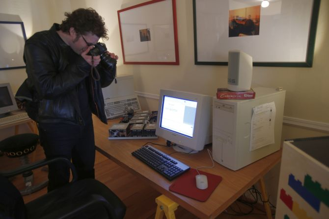A photographer takes picture of a computer inside Google co-founder Larry Page's original office on Google's 15th anniversary in Menlo Park, California.