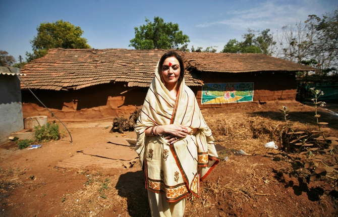 Nita Ambani poses in front of a hut during a 'Reliance Bij - Bharat India Jodo' campaign at Salarpur village, south of Ahmedabad.