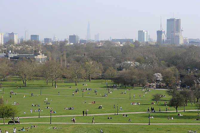 People sit in the sunshine on Primrose Hill in north London, United Kingdom.