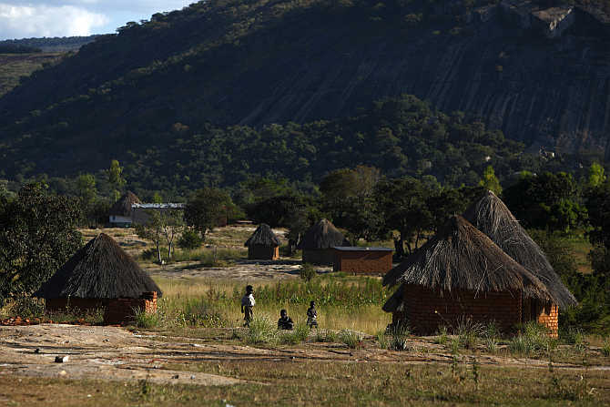 Children play outside thatched roof huts in Domboshawa, around 80km east of Harare, Zimbabwe.