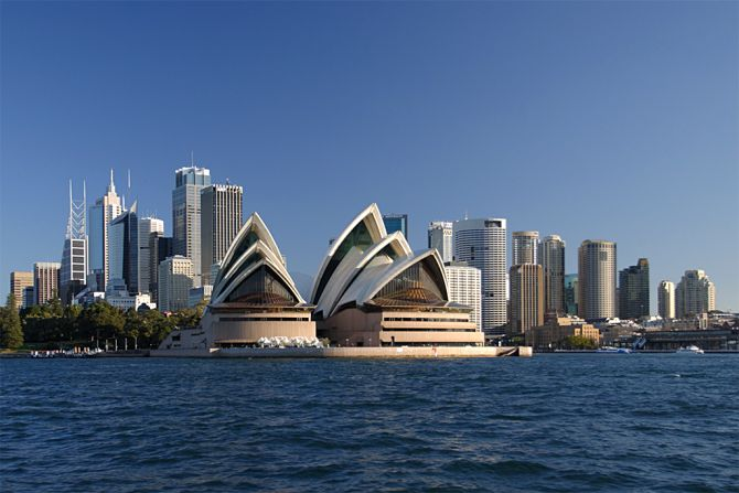 The Sydney Opera House viewed from the water with the city skyline behind.