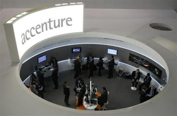 Visitors look at devices at Accenture stand at the Mobile World Congress in Barcelona.