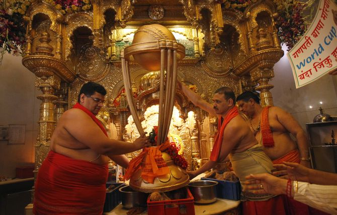 Hindu priests hold a replica of the Cricket World Cup trophy during a puja, or blessing ceremony, at the Siddhivinayak temple in Mumbai.
