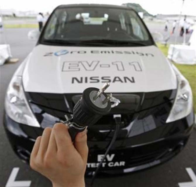 A 100 volt AC power cable is displayed in front of Nissan Motor Co's new electric vehicle.