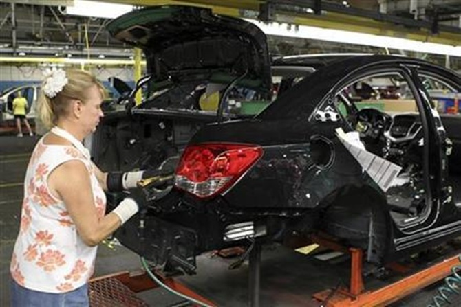 A worker installs the rear tail light assembly on the new Chevrolet Cruze car as it moves along the assembly line at the General Motors Cruze assembly plant in Lordstown, Ohio.