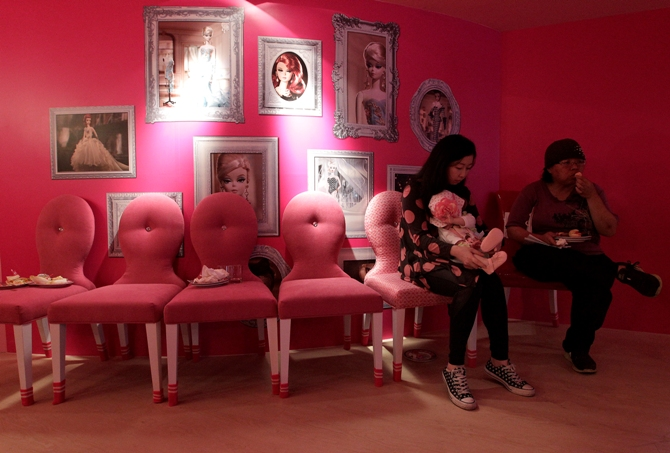 Customers eat dessert during the media preview of a Barbie-themed cafe in Taipei.