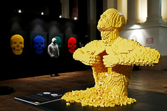 The art work titled Yellow, which is made out of Lego bricks, is seen as a visitor poses next to another Lego art work titled Skulls (L) during 'The Art of the Brick' exhibition at the Brussels Stock Exchange.