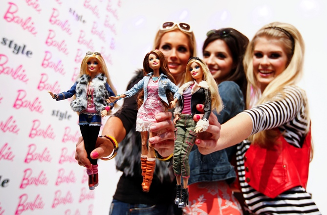 Models pose with the popular 'Barbie' doll during the press preview of the 65th International Toy Fair in Nuremberg January 28, 2014.