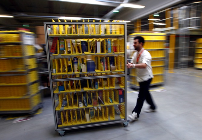 A worker collects items to pack into boxes at Amazon's logistics centre in Graben near Augsburg.