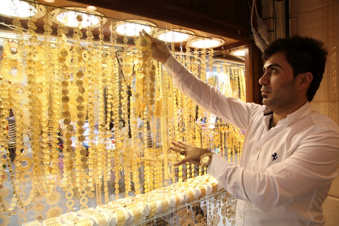 A goldsmith shop owner displays gold pieces at a gold market.
