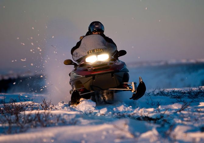 Guest ride a Snowmobile at the Sorrisniva Igloo Hotel.