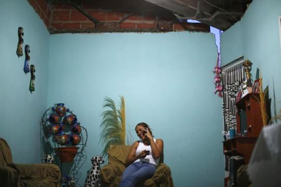Thais Ruiz, 36, talks on the telephone and drinks coffee as she sits under a crack in the roof of her living room on the 27th floor.