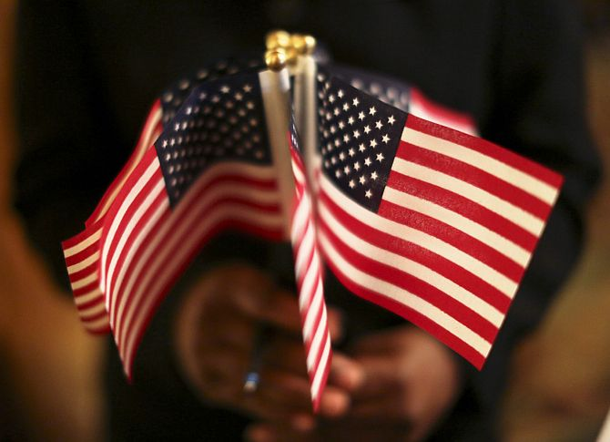 A woman holds a cluster of U.S. flags during a U.S. Citizenship and Immigration Services naturalization ceremony in Oakland, California.