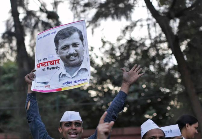 A supporter of Aam Aadmi Party (AAP) holds a portrait of Arvind Kejriwal.
