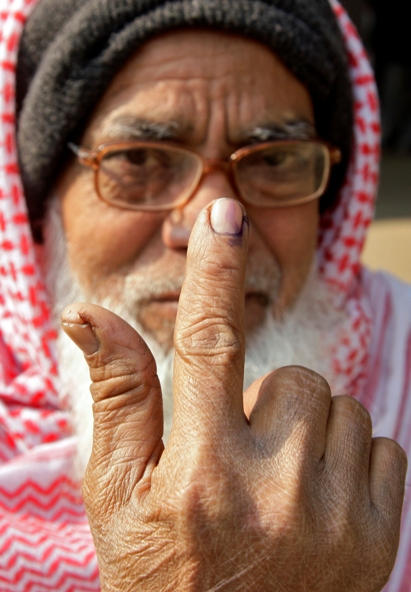 A voter shows his ink-marked finger after casting his vote, outside a polling station.